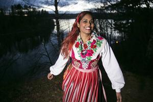 Padma Schreweilus i Leksandsdräkt framför Siljan.