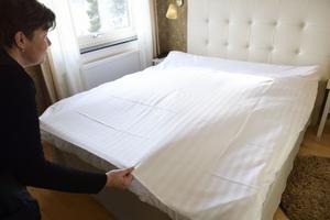 Bäddproffset Agnieszka Gladka lyfter överdelen av påslakanet och släpper in luft, och sen släpper hon det så att lakanet faller slätt över sängen. Platta inte med händerna!