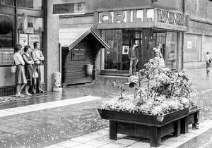 En störtskur över Holmgatan 1976, kvinnor i kjol och mannen i utsvängda jeans söker skydd där Domushuset tar slut.