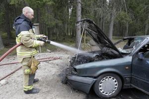 Räddningspersonal sköter om eftersläckningen i väntan på bärgning.