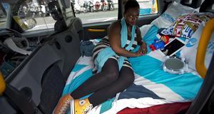 Jennifer Tetteh, pr-konsult, poserar i en av Londons taxibilar som gjorts om till hotell under OS.