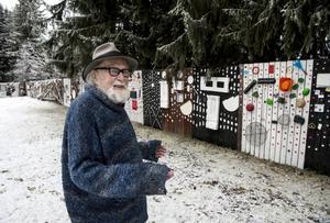 Curt Agge vid planket i parken i Gimåfors - bland annat har det hittills gått åt 9000 kapsyler för att pryda det.