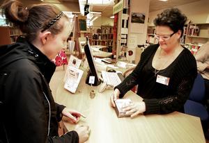 Utlåningen minskar i landet. Samtidigt är det fler som går över till att lyssna på böcker och det märks på Smedjebackens bibliotek. Här lånar Emma Gustavsson en ljudbok av Marie Ohlsson. Foto:Thomas Isaksson