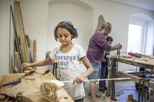 Alisha Hauffman, 10 år, bygger ett litet hundhus till sina trähundar som hon gjort tidiagre i träslöjden. – Det är roligt att vara här. För man får bygga saker, säger hon.