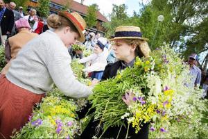 Jamtlis personal har fullt upp att fästa blommorna kring stången . Det bildas en kö av människor som kommer med blommor.