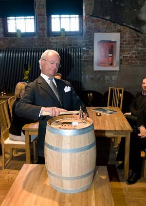 Här hamrar kung Carl Gustaf in sin namnskylt på sitt eget whiskyfat av märket Mackmyra.