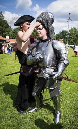 Erik Kullander får hjälp att få på sig sin 30 kg tunga riddarutrustning från tidigt 1400-talt. Varmt, jovisst, som en bastu. Dock näst intill osårbar!