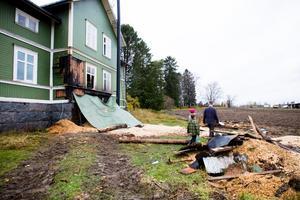Fasaden har fått stora skador efter branden. Flisförrådet ligger krossat i förgrunden.
