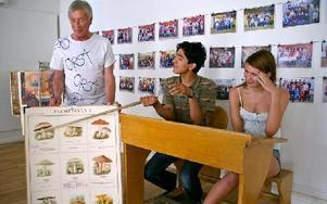 Bildarkivets föreståndare Mikael Stålberg och kulturhusets sommarjobbare Faizullah Sadat och Emelie Olsson med en gammal plansch och en skolbänk av äldre modell.FOTO: JENNIE-LIE KJÖRNSBERG