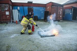 Med bestämt grepp om släckaren tar brandmannen Christer Lundgren hand om fatet med den brandfarliga vätskan.