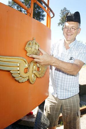 Thomas Allander skruvar fast SJ:s gamla emblem.