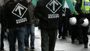 Medlemmar av Svenska Motståndsrörelsen under en demonstration - under poliseskort - i Stockholm.