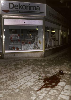 Mordplatsen med en stor blodpöl efter Sveriges statsminister Olof Palme som blev skjuten till döds omkring tjugo minuter över elva på kvällen den 28:e februari 1986 vid hörnet av Sveavägen och Tunnelgatan, när han och hans fru Lisbet promenerade hem efter ett biobesök tidigare på kvällen.