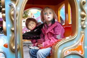 Systrarna Ebba och Tilda Skaret förbereder sig för en tur i karusellen.