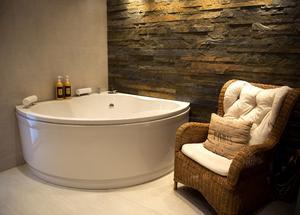 Fondväggen i skiffer och rottingfåtöljen ger en värme till badrummet.