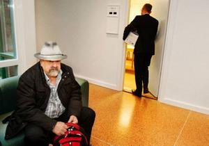 Nils-Eric Johansson väntar på att hans            ärende ska ropas upp i tingsrätten. I den röda ryggsäcken har han alla argument som han tänker använda i sitt försvarstal. Foto: Ulrika Andersson