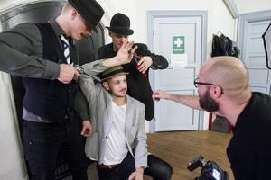 Vid en av fotograferingarna håller Stefan Norman i en avbitartång placerad runt pekfinger samtidigt som Pär Norgren riktar en pistol mot David Axelssons huvud.