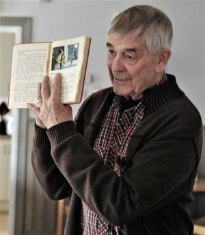 Malte Enmalm visar uppläseboken Sörgården från 1943.  >