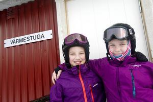 Joline Skoghfrost och Alice Jonasson utanför värmestugan.