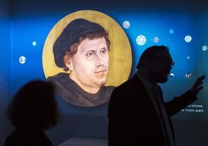 Besökare framför en videoinstallation med ett porträtt av Martin Luther i utställningen