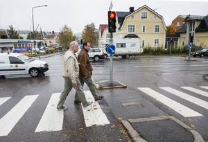 Peter Sandström hjälper Lennart Andersson över gatan. Bergsgatan är en av de hårdast trafikerade vägarna i Sundsvall och extra problematiskt är det för synskadade.
