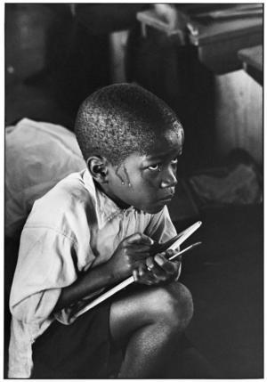 Skolpojke jobbar hårt trots att han får sitta på golvet. Ernest Cole fångade de svarta barnens intensiva kunskapstörst.Foto: Ernest Cole Family Trust