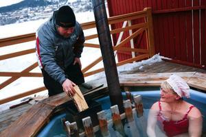 – Jag försöker hålla + 40 grader i vattnet, för det är lagomt varmt, konstaterar badmästare Edvinssson innan lägger in ett par björkklampar till i kaminen. Till höger i rosa huvudbonad catrine Edlund.