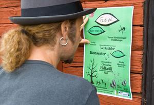 Richard Svanström sätter upp en festivalaffisch vid dörren till kulturhuset.