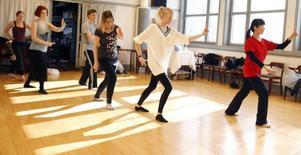 Eleverna lär sig grunderna till kinesisk svärdsdans.
