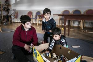 Tre barn från Syrien hittade snabbt en låda med enkla leksaker.