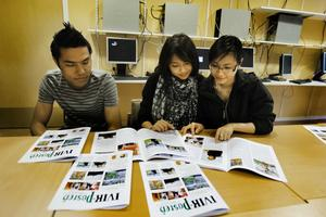 Meisam Rezaei, Ning Chansawong och Thao Luong tittar i sin nytryckta tidning som har allt från serier till längre reportage.