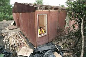 Den romske aktivisten Josef Stojka i Ostrava i Tjeckien tittar ut genom fönstret på en barackliknande byggnad som fungerar som bostad för en romsk familj, vars hem har förstörts i en översvämning 1997.