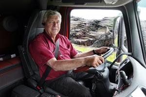 Curt Göransson bakom ratten i en av sina lastbilar. I bakgrunden blötlagt virke.