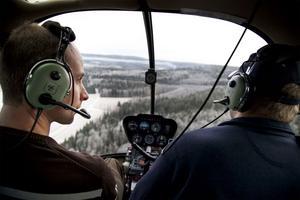 Mikael Thybeck och Mikael Fröberg spanar efter stormskadad skog från sin helikopter.