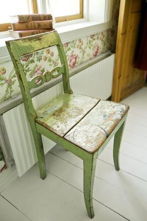 I sovrummet. En sliten stol och gamla böcker är fina detaljer i sovrummet.