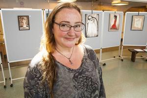 Ulrika Lepik framför några av sina tavlor som hänger i Ljushallen till slutet av maj.