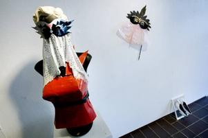 Precis vid ingången hänger en korsett och en mask gjord av papper, tejp och tyg.