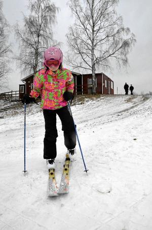 Första åket. Wilma Oskarsson spänner på sig skidorna inför premiärturen i stora backen. I backen finns snö, men runt omkring täcker snön inte gruset.