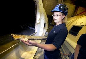 Vid ett massafilter står Maria Larsson, Söderhamn och tar med en lång träspade det prov på massan som ska göras varannan timme.