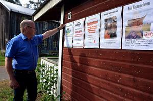 Anders Mannqvist, ordförande Borgsjö hembygdsgårdsförening, vid affischväggen som avslöjar en del av det som är på gång i sommar.