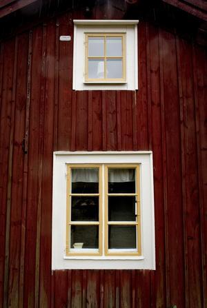 Den gamla timmerstugan har någon gång under årens lopp klätts med panel. Ockrafärgen runt fönstren kommer kanske att målas även på ytterdörren.