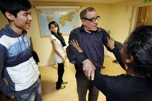 Luwam Tosheme från Eritrea försöker härma hållningen. Dansläraren Abbe Elchamimi pratar på, ännu ovetandes om att hans elever förstår mycket lite svenska. I armarna håller han Helen Alemseged tkele.