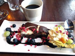 Ljus och mörk chokladkaka med tillbehör i form av blåbär, vindruvor och grädde.