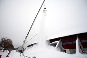 Problem med snön. Så här har det sett ut vid Göransson Arena så fort det snöat. För att undvika takras har fastighetsbolaget skottat taket med hjälp av lyftkran och skopa. Men nu görs ett försök med att få snön att glida av på ett naturligt sätt.