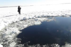 En kvinna tittar på hålet efter den meteorit som bland annat slog ned i en sjö i ryska Tjeljabinsk.