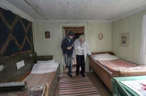 I fäbodstugan bodde fäbodstintan på somrarna och ibland skogsarbetare på vintrarna. Lars Mittjas hjälper och visar en av besökarna från Backsippan.