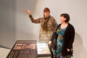Helena Arnell och Ingrid Eriksson vid Army of Lovers scenkläder. På och i skrivbordet finns information om designern Camilla Thulin. Under  kvällens vernissage utlovas premiärkänsla med bubbel och underhållning av västeråsarna Anton Caringer och makeup-artisten Agnes Arnell.