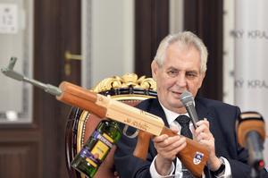 President Milos Zeman håller och en träreplika (med vodkaflaska) av en AK-47 med texten