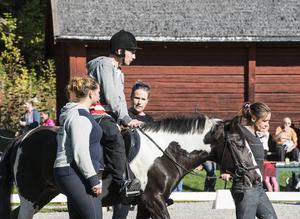 Fredrik Norberg som var med om en fallolycka för ett år sedan visar hur han rehabiliteringstränar sina muskler. Ponnyn Mona leds av Lotta Bylund och på var sida om ponnyn går Amanda Ahlström och Fredriks personliga assistent Ida Eriksson.