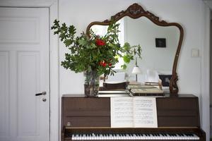 Ovanpå pianot står en vacker spegel som Ida har köpt på auktion samt en stor bukett av kvistar och bär från trädgården – en hållbar bukett.